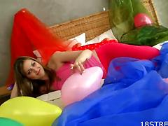 Playful teen girl grabs a sex toy for a kinky solo play